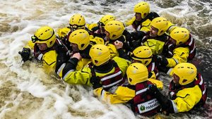 Water Rescue Team using wading pole to traverse a river
