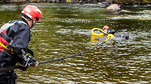 Swiftwater rescue training with flotation collar attachment rescuing casualty from river